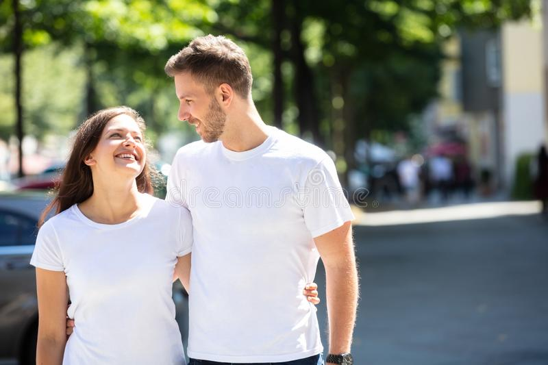 Pares felices que se colocan en la calle fotografía de archivo libre de regalías