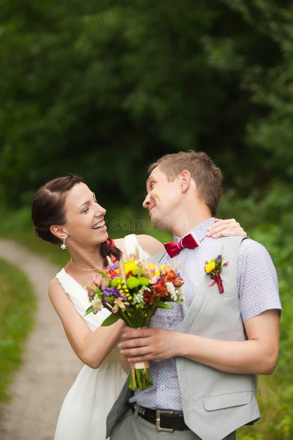 Pares felices que se colocan en parque verde, besándose, sonriendo, riendo imágenes de archivo libres de regalías