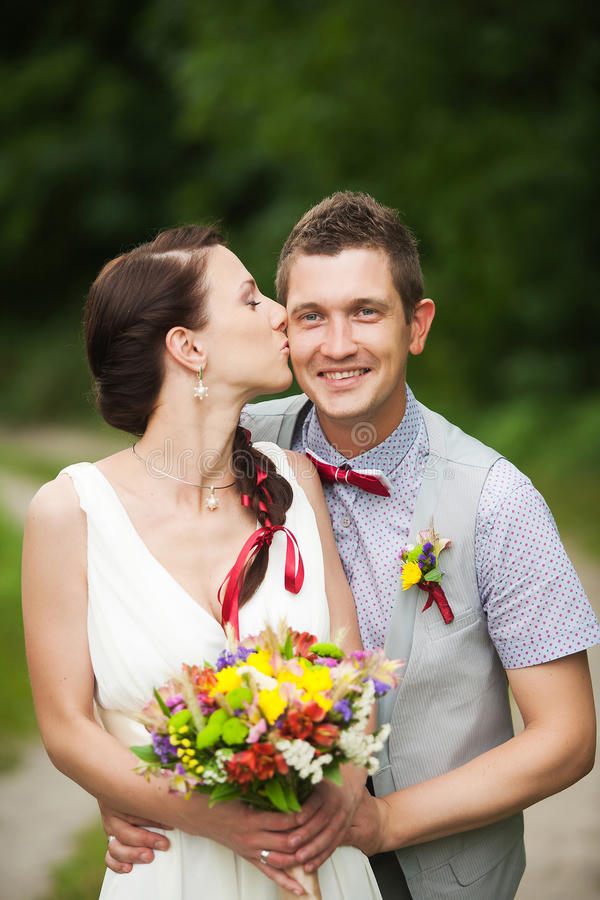 Pares felices que se colocan en parque verde, besándose, sonriendo, riendo foto de archivo libre de regalías
