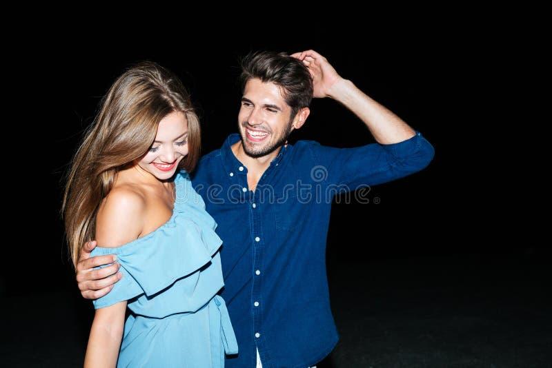 Pares felices que se colocan y que abrazan en la noche en la playa imagenes de archivo
