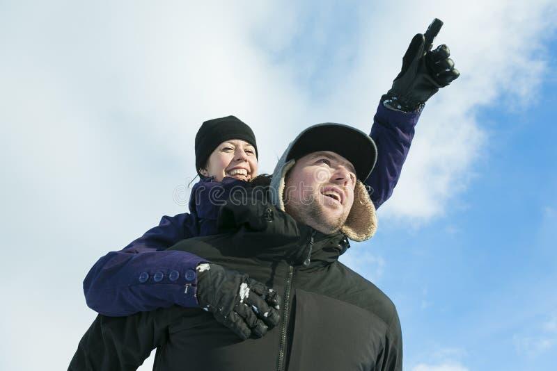Pares felices que se divierten al aire libre nieve Invierno imágenes de archivo libres de regalías