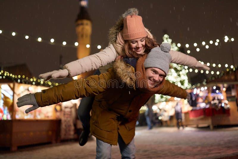 Pares felices que se divierten en el mercado de la Navidad imagen de archivo libre de regalías