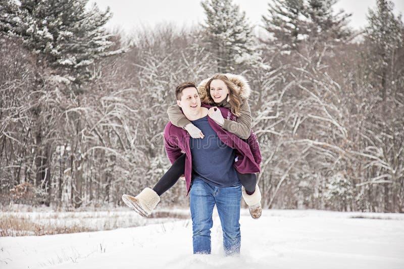 Pares felices que se divierten en nieve foto de archivo libre de regalías