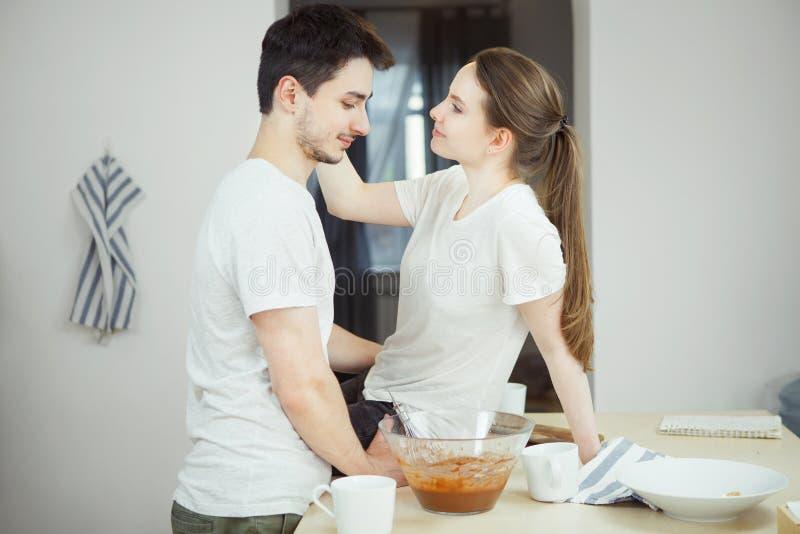 Pares felices que se divierten junto en cocina foto de archivo