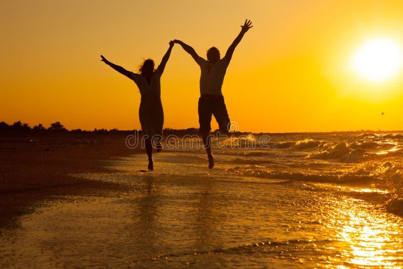 Pares felices que se ejecutan en la playa imagen de archivo