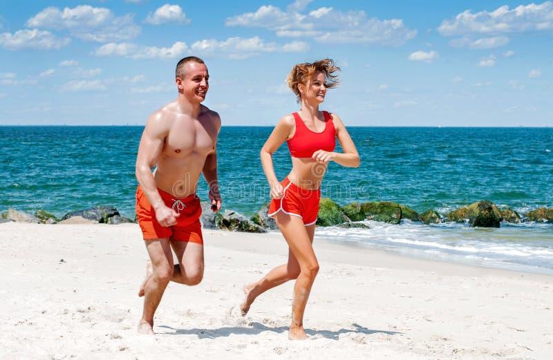 Pares felices que se ejecutan en la playa Hombre y mujer que activan en la orilla de mar fotografía de archivo libre de regalías