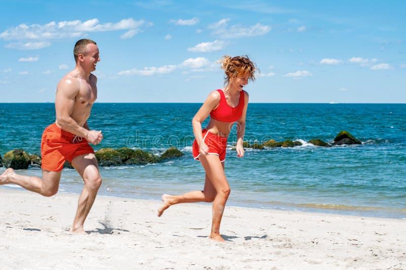 Pares felices que se ejecutan en la playa Hombre y mujer que activan en la orilla de mar imagen de archivo libre de regalías