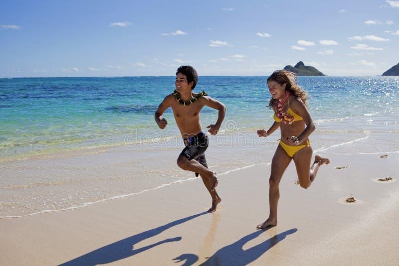 Pares felices que se ejecutan en una playa de Hawaii imágenes de archivo libres de regalías