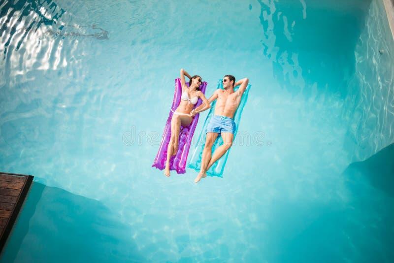 Pares felices que se relajan en balsa inflable en la piscina fotos de archivo libres de regalías
