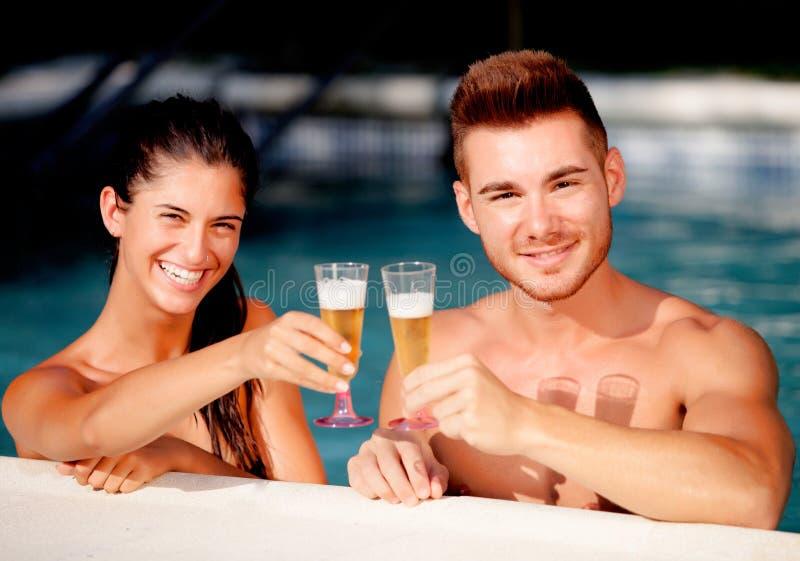 Pares felices que se relajan en la piscina en el verano imagen de archivo