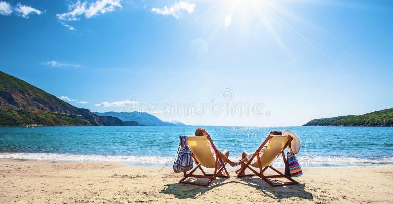 Pares felices que se relajan en la playa imagenes de archivo