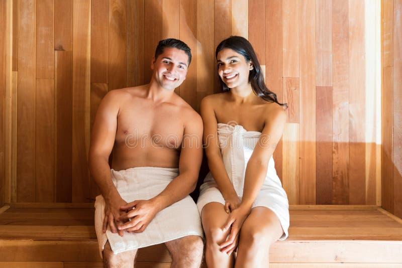 Pares felices que se relajan en la sauna durante vacaciones fotos de archivo libres de regalías