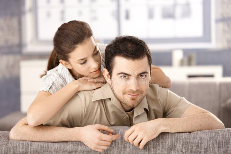 Pares felices que se sientan en el sofá que se abraza imagen de archivo libre de regalías