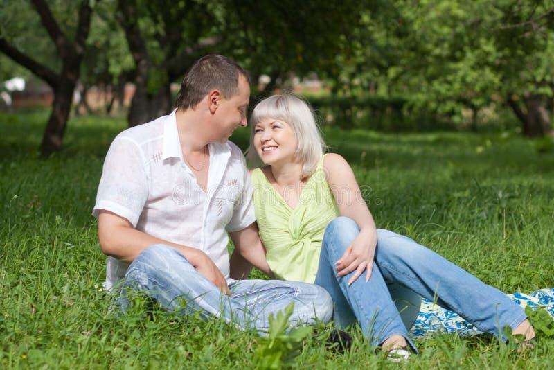 Pares felices que se sientan en la hierba foto de archivo libre de regalías