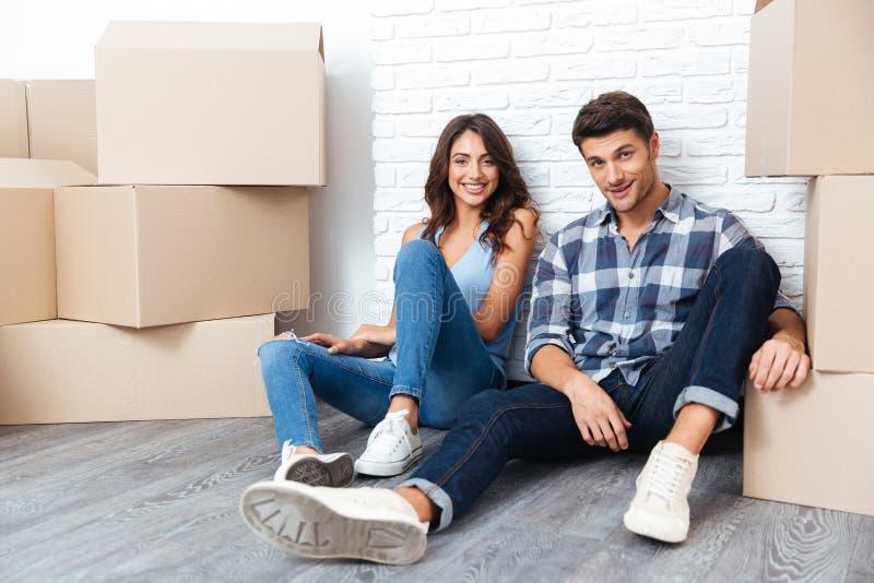 Pares felices que se sientan en piso alrededor de las cajas después de comprar la casa fotos de archivo