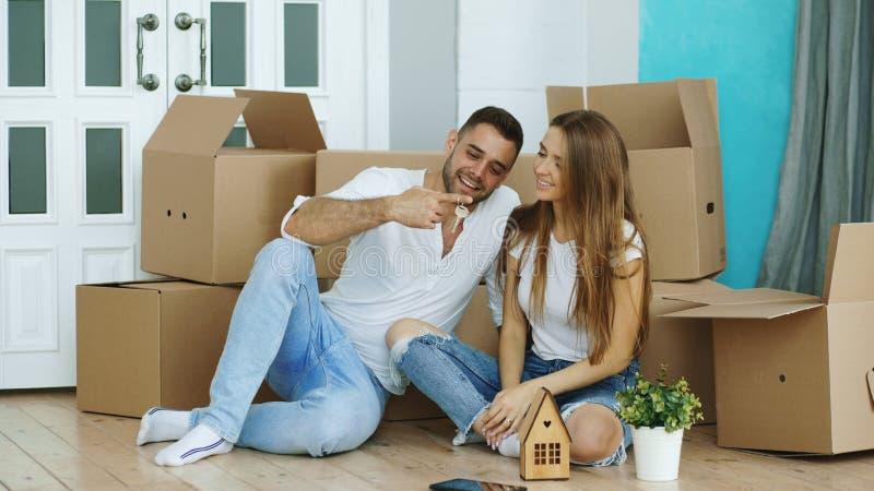 Pares felices que se sientan en piso en nueva casa El hombre joven da llaves a su novia y a besarla fotos de archivo libres de regalías