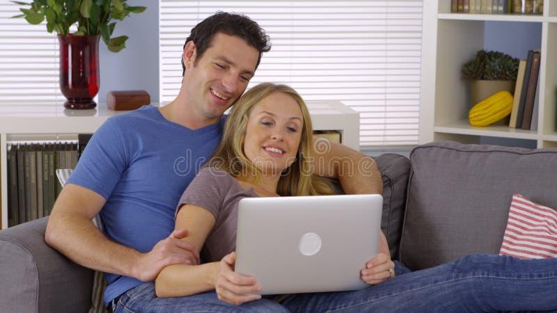 Pares felices que se sientan en sala de estar con el ordenador portátil foto de archivo