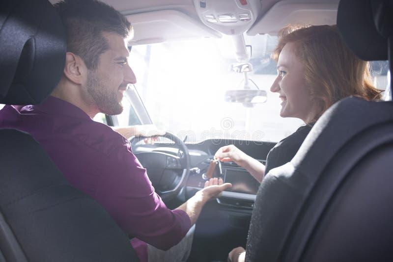 Pares felices que se sientan en un nuevo coche Novia que da llaves del coche a foto de archivo libre de regalías