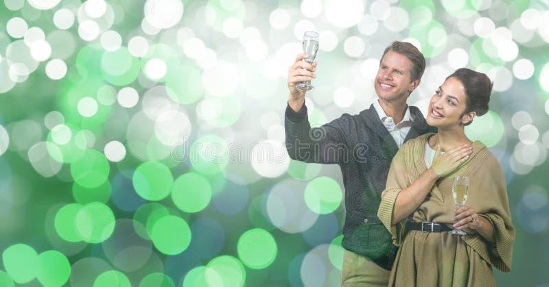 Pares felices que sostienen las flautas de champán sobre bokeh foto de archivo