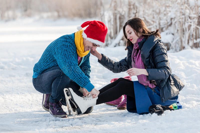 Pares felices que tienen patinaje de hielo de la diversión en pista al aire libre foto de archivo libre de regalías