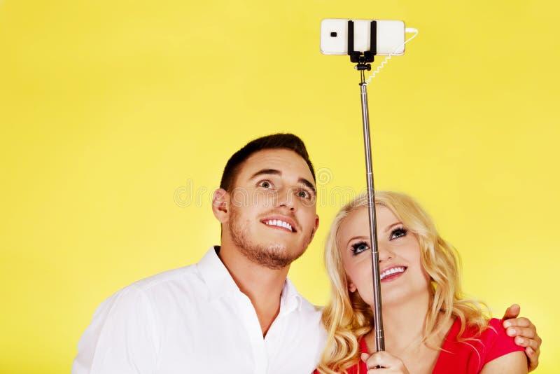 Pares felices que toman la foto del selfie con el palillo del selfie imagenes de archivo