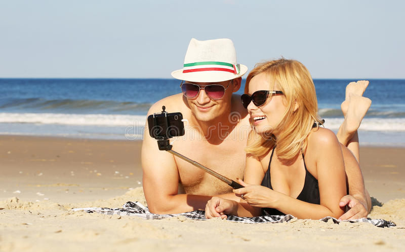 Pares felices que toman la foto del selfie con el palillo del selfie en la playa imágenes de archivo libres de regalías