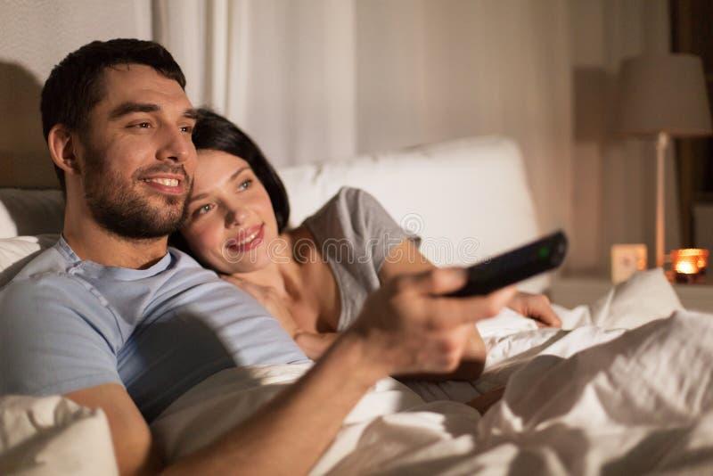 Pares felices que ven la TV en cama en la noche en casa imagen de archivo