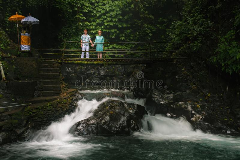Pares felices que viajan en Bali, en el río del puente, Ubud honeymoon fotos de archivo