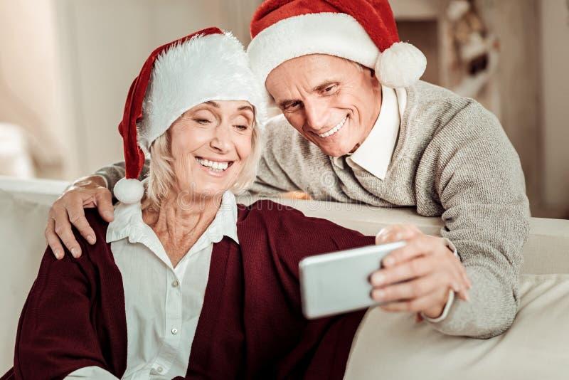 Pares felices satisfechos que hacen la foto y la sonrisa imagenes de archivo