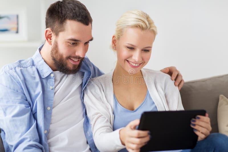 Pares felices sonrientes con PC de la tableta en casa fotografía de archivo libre de regalías