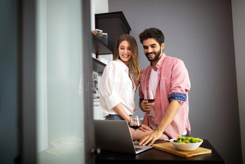 Pares felices usando el ordenador portátil mientras que desayunando en cocina imagenes de archivo
