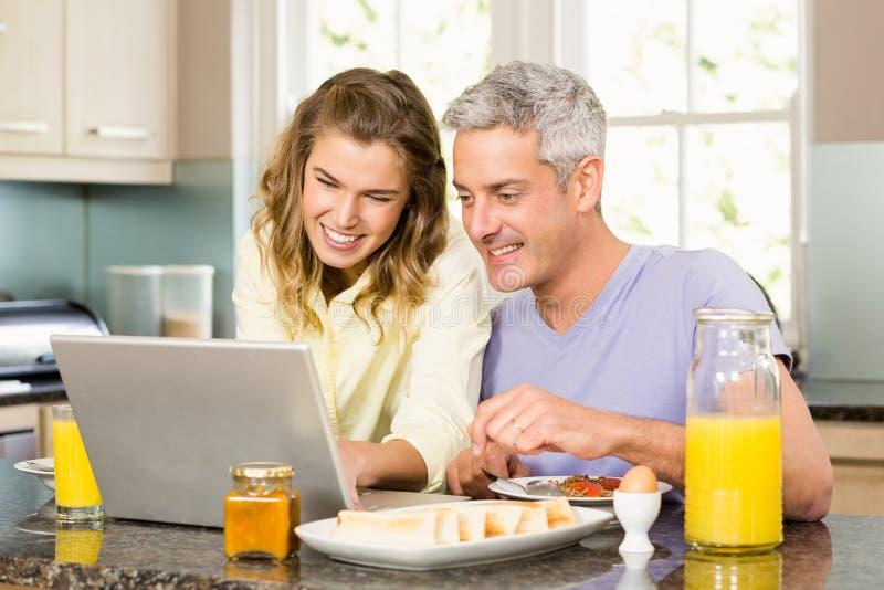 Pares felices usando el ordenador portátil y el desayuno el tener fotos de archivo libres de regalías