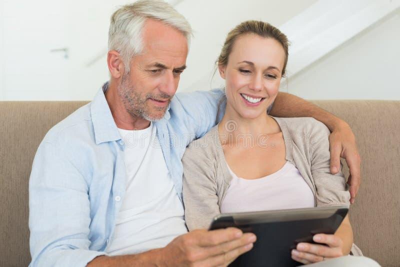 Pares felices usando la PC de la tableta junto en el sofá imagen de archivo
