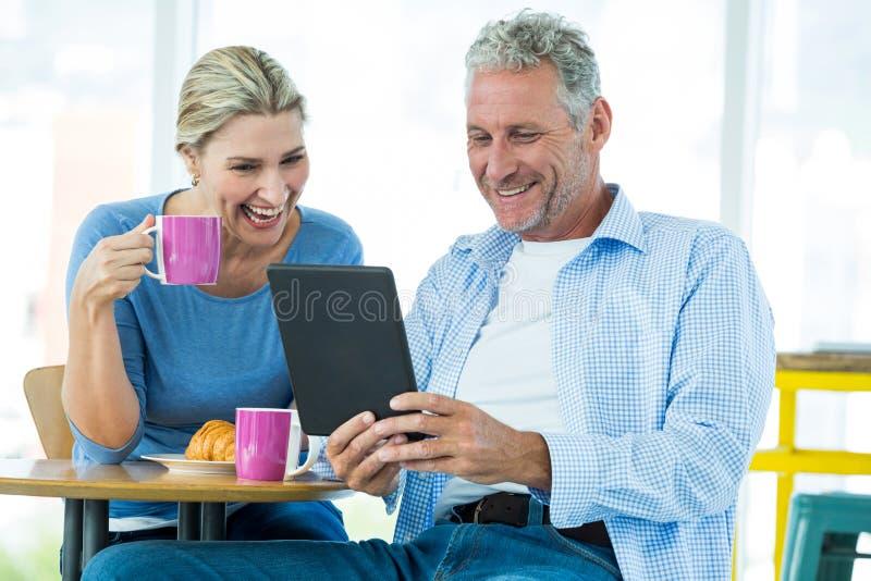 Pares felices usando la tableta de Digitaces foto de archivo