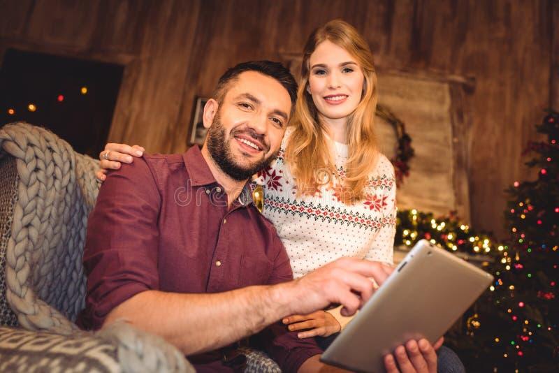 Pares felices usando la tableta digital mientras que se sienta en butaca gris imagen de archivo libre de regalías