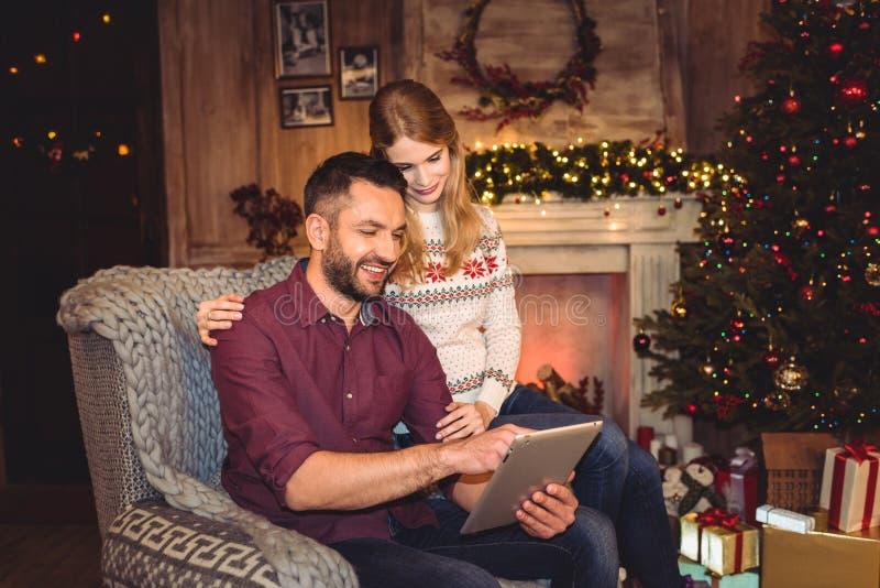 Pares felices usando la tableta digital mientras que se sienta en butaca gris fotos de archivo libres de regalías