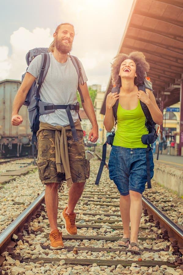 Pares felices y hermosos de los turistas que caminan en las pistas en foto de archivo