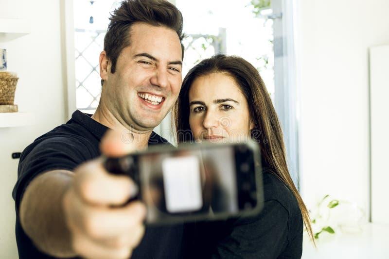 Pares felices y sonrientes que hacen un selfi en casa Junte tomar una imagen con el teléfono celular fotografía de archivo