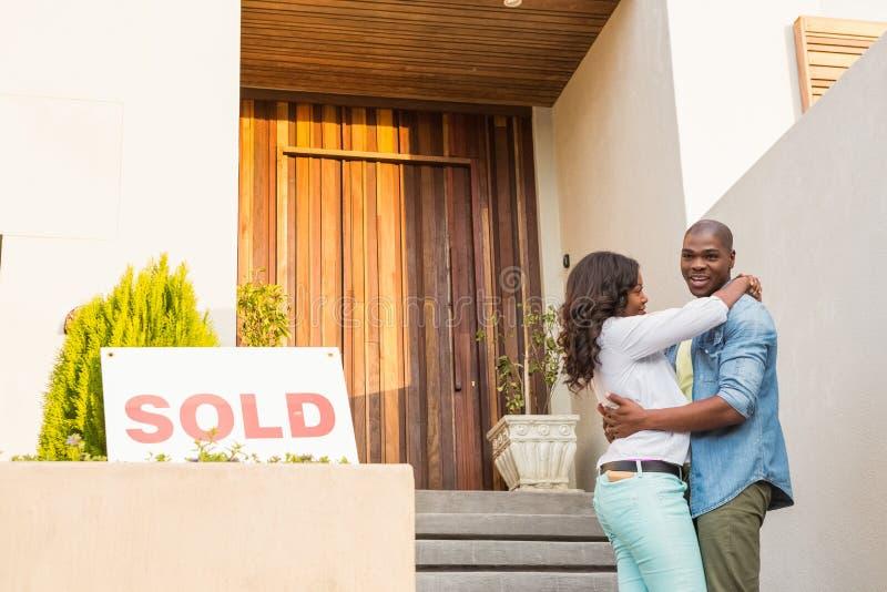 Pares felizes após ter comprado a casa nova foto de stock