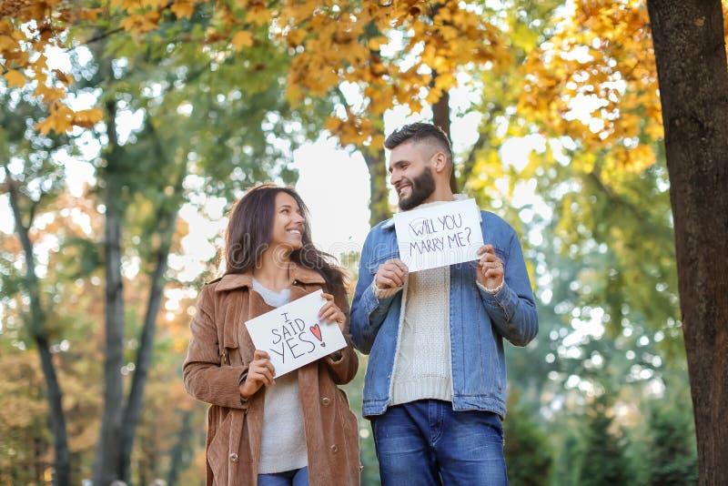 Pares felizes após ter feito a proposta no parque do outono foto de stock