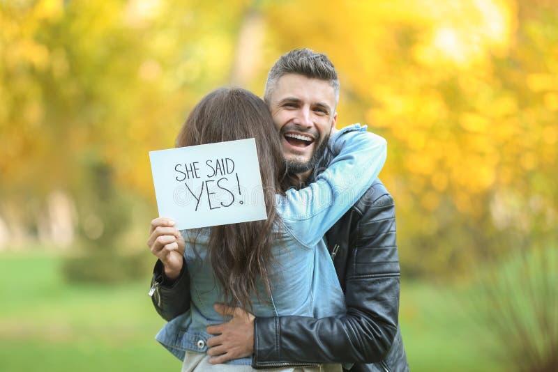 Pares felizes após ter feito a proposta no parque do outono imagem de stock royalty free