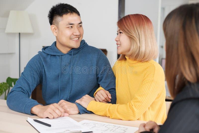 Pares felizes asiáticos que compram a casa nova com o agente do corretor de imóveis com smili fotos de stock