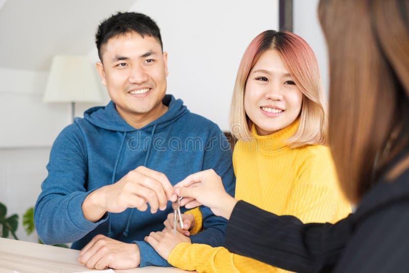 Pares felizes asiáticos que obtêm a chave com o agente do corretor de imóveis com a cara de sorriso na casa nova casa nova de com foto de stock royalty free