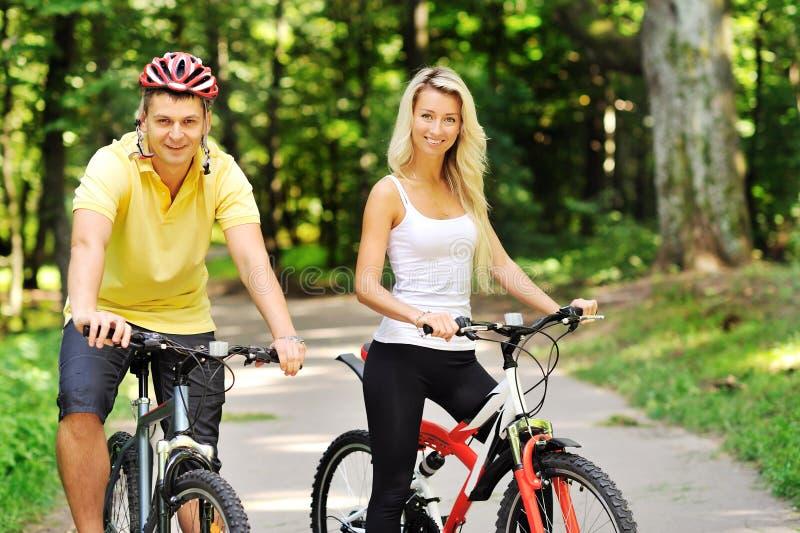 Download Pares Felizes Atrativos No Bicicletas Em Um Campo Foto de Stock - Imagem de companhia, fora: 29836860