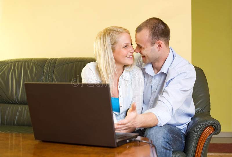 Pares felizes atrativos usando o portátil em casa. fotografia de stock royalty free