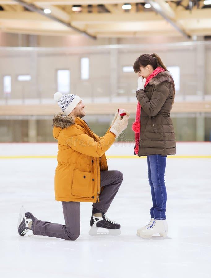 Pares felizes com anel de noivado na pista de patinagem imagens de stock