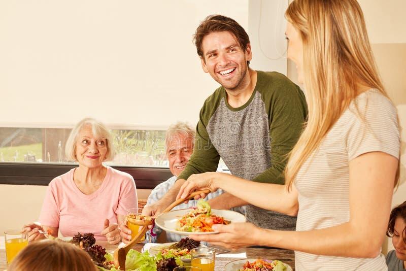 Pares felizes com as avós na mesa de jantar fotos de stock