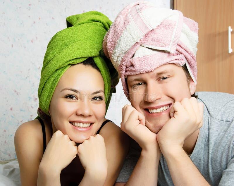 Pares felizes com as toalhas em suas cabeças fotografia de stock royalty free