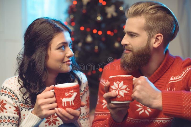 pares felizes com bebidas quentes na vista do Natal imagem de stock royalty free