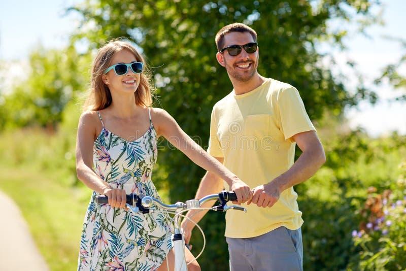 Pares felizes com a bicicleta no país fotografia de stock